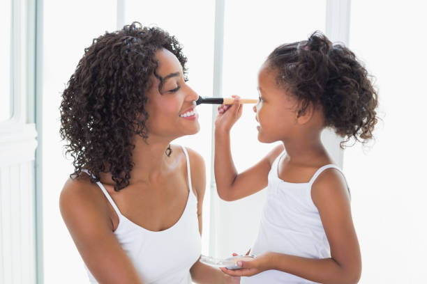Cute daughter putting makeup on her mothers face at home in the bathroom